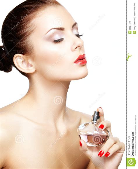 Young Woman Applying Perfume On Herself Isolated On White